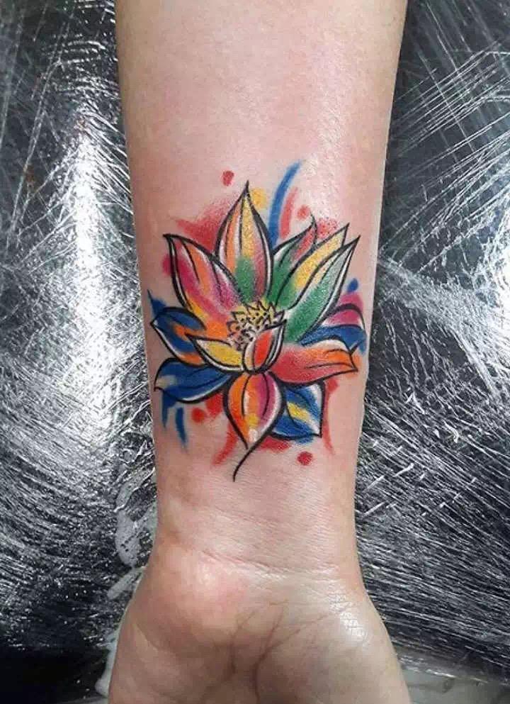 纹身是一种潮流,而且也是一种趋向年轻化的时尚,越来越多的年轻人开始接受和尝试这种艺术形式。福州的化妆师董先生在自己的手腕处纹刻了一款七彩莲花纹身图案,每天董先生都会通过双手来打造各种美艳的造型,他也希望每次看到手腕处的七彩莲花,可以带给自己无限的灵感创意,做出更好的造型。 福州的董先生手腕处所纹刻的这款莲花,黑色的线条勾勒出七彩莲花的轮廓,逐渐舒展开的莲花绽放的非常灿烂。上色方式比较有创意,渲染的手法将红色、黄色、粉色、蓝色、绿色、橙色等多种颜色混合在一起,自由而随意的上色,让七彩莲花绽放的更加绚丽多彩